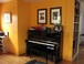 Music area: Yamaha upright piano near shelves of sheet music, with guitar tucked into corner