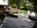 A charming water mill in surrounding countryside.