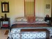 Master Bedroom: The feel is world traveler with an emphasis on Asia and Africa with an understated elegance. King size bed, with view to the ocean over the trees.
