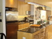 Kitchen w/ view into Living Room: Fully equipped gourmet kitchen w/ granite counter tops, maple cabinets, stainless steel appliances